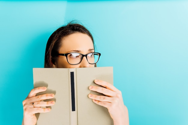 Beautiful young woman covering her face with a book while looking aside with space for copy