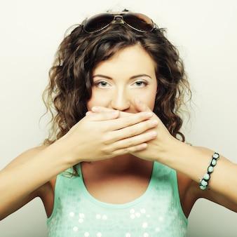 Красивая молодая женщина, закрывающая лицо рукой