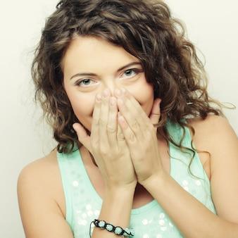 Красивая молодая женщина закрыла лицо рукой