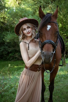 Beautiful young woman in a cowboy hat near a horse on nature in the park