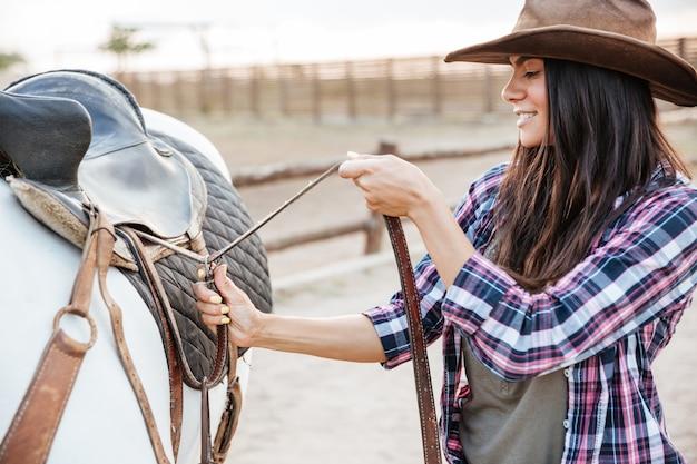 Красивая молодая женщина скотнице стоя и ставя седло на лошадь