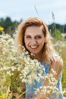 Beautiful young woman on the daisy flowers field