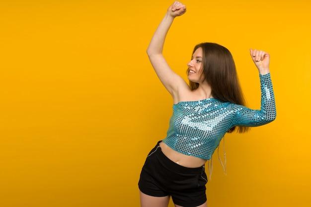 노란색 배경에 포즈 반짝이 블루 케이프에서 아름 다운 젊은 여자 댄서.