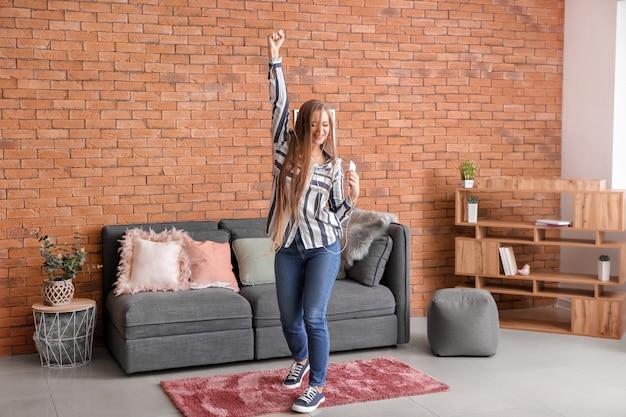 Красивая молодая женщина танцует дома