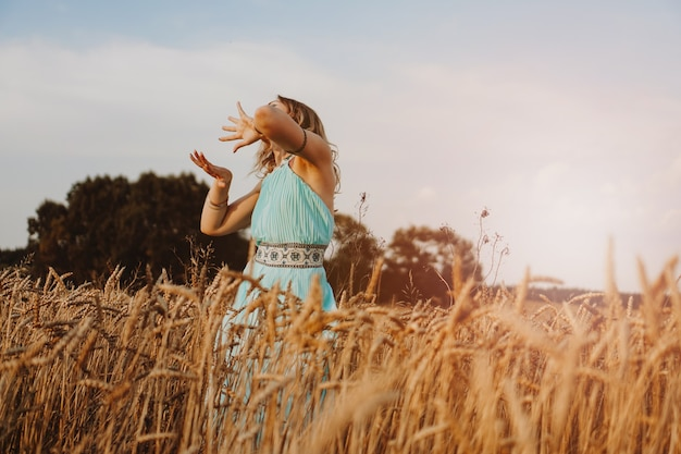 Beautiful young woman dancing in the field at sunset