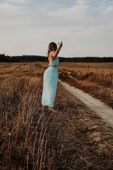 해질녘 필드에서 춤추는 아름 다운 젊은 여자