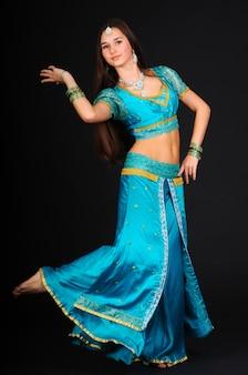 Красивая молодая женщина танцует индийский танец в традиционной одежде