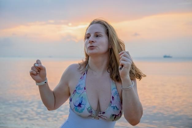 Красивая молодая женщина танцует на фоне заката у моря