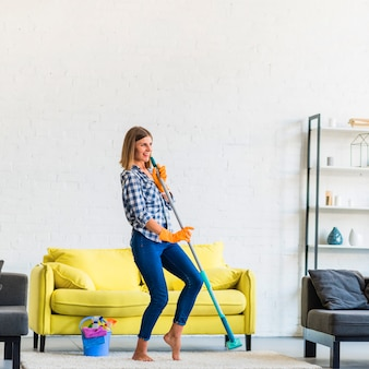 Beautiful young woman dancing with mop in the living room