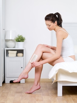 Beautiful young woman depilating her attractive legs by waxing at home - indoors