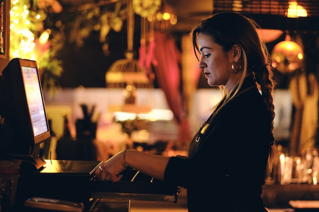 A beautiful young woman at the desk in a restaurant