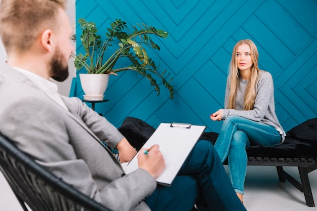 Beautiful young woman discussing her problems with male psychologist sitting on chair