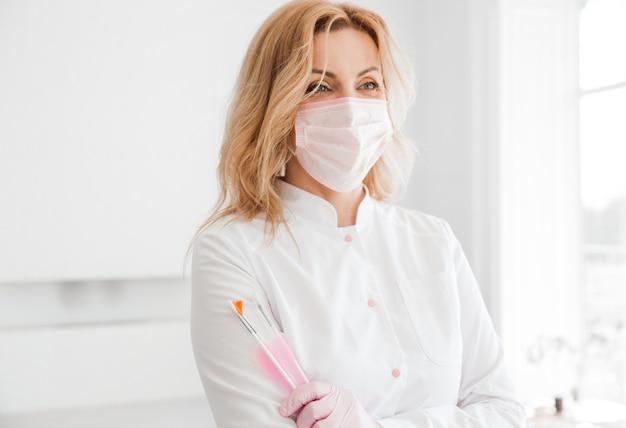 Красивая молодая женщина-врач-косметолог в белой форме и защитной маске на лице позирует с кистями в руках.