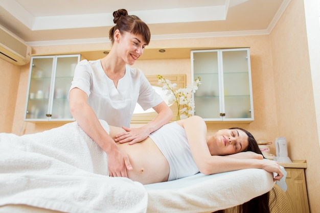Beautiful young woman doctor massage therapist in a cosmetology room doing a massage to a pregnant girl with long hair