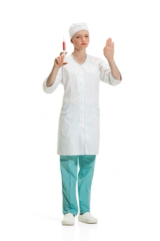 Beautiful young woman doctor in medical robe holding syringe in hand.
