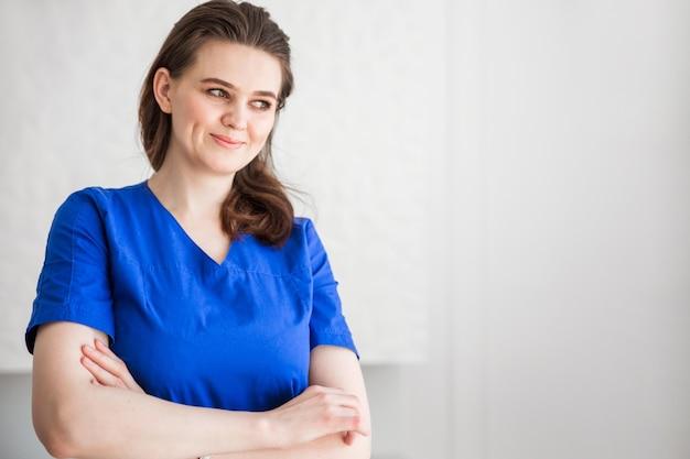 青い医療スーツでポーズをとる美しい若い女性医師。