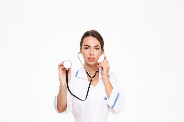Beautiful young woman doctor wearing uniform standing isolated over white wall, using stethoscope