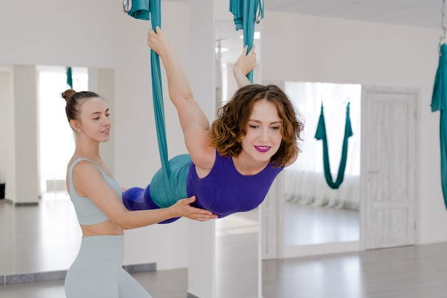 Красивая молодая женщина занимается воздушной йогой с тренером в студии