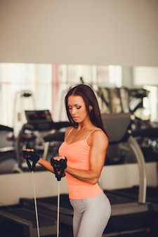 Beautiful young woman doing exercise at the gym. athletic build