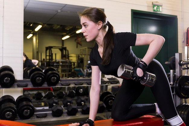 Beautiful young woman doing exercise with dumbbell