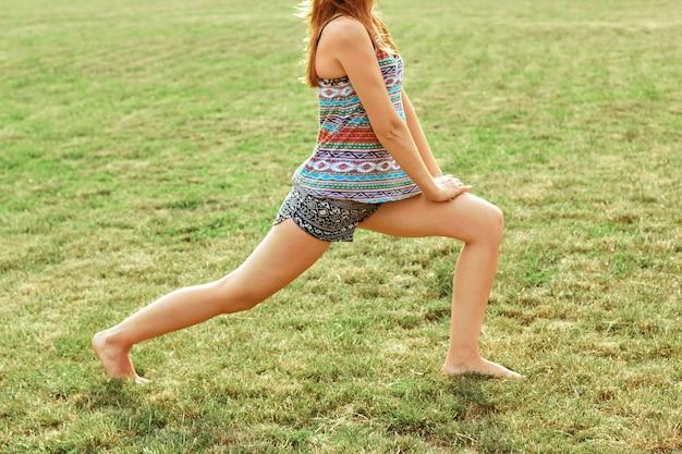 公園で練習をしている美しい若い女性。健康とヨガのコンセプトです。フィットネスとスポーツ