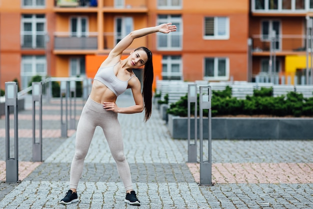 Beautiful young woman doing exercises outdoors. gorgeous fitness female training hard.