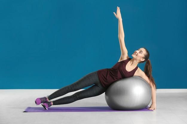 Красивая молодая женщина делает фитнес-упражнения с мячом дома