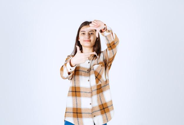 手のひらと指を使用してフレームをやっている美しい若い女性。
