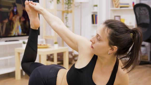 リビングルームで彼女の柔軟性の練習をしている美しい若い女性。