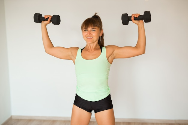 Beautiful young woman doing home workout with dumbbells