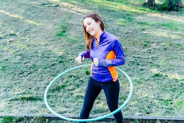 Красивая молодая женщина делает обруч на закате в парке поинт концепции спорта художественной гимнастики личной гигиены