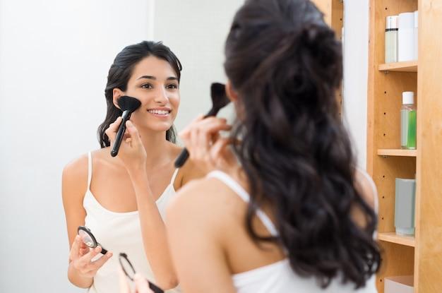 Красивая молодая женщина делает макияж в своей ванной комнате