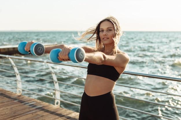 ビーチでダンベルと朝の運動をしている美しい若い女性。