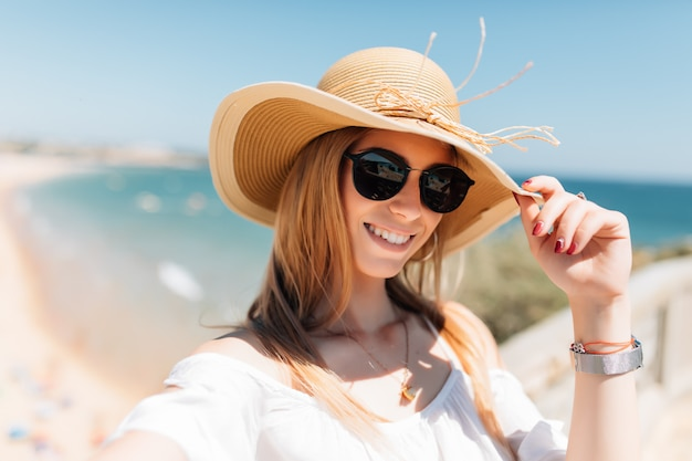 Beautiful young woman doing selfie on the beach on ocean
