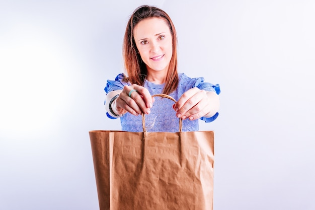 Beautiful young woman doing showing in front a cardboard shopping bag. plastic free concept