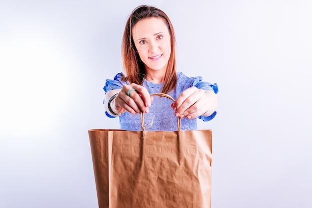 Красивая молодая женщина делает показ перед картонной хозяйственной сумкой. концепция без пластика