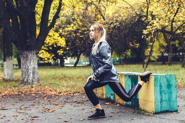 Beautiful young woman doing sports exercises in a city park at rainy weather.