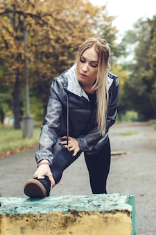 Beautiful young woman doing sports exercises in a  park at rainy weather.