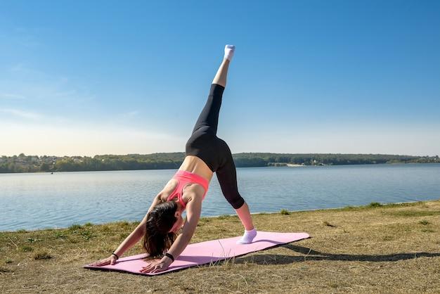 公園で朝の作業時間の前にストレッチ運動をしている美しい若い女性