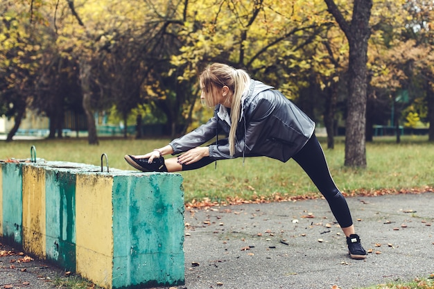 Beautiful young woman doing stretching  exercises in a city park at rainy weather.