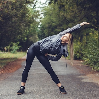 Beautiful young woman doing stretching sports exercises in a city park at rainy weather.