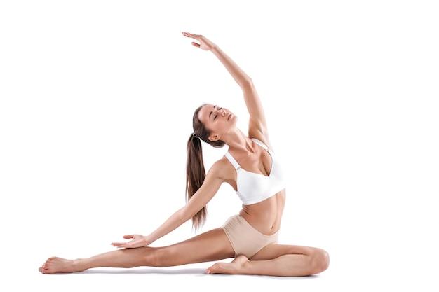 ヨガやピラティス運動をしている美しい若い女性は、白い背景で隔離。健康的な生活と体と精神の発達のバランスの概念。全長