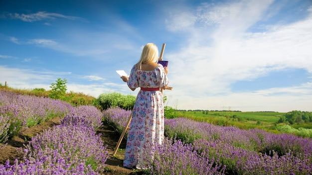 朝のラベンダー畑に絵を描く美しい若い女性。