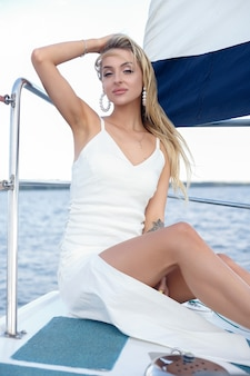 Beautiful young woman in a dress on a yacht