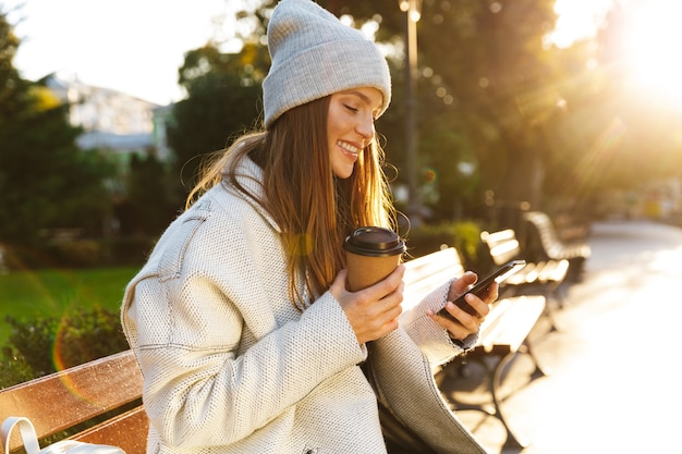 Beautiful young woman dressed in autumn coat and hat sitting on a bench outdoors, drinking coffee, using mobile phone