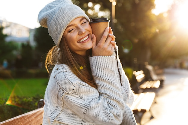 Beautiful young woman dressed in autumn coat and hat sitting on a bench outdoors, holding cup of warm coffee