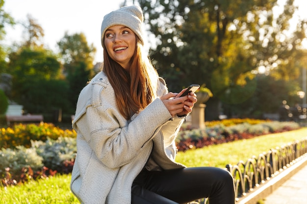 Beautiful young woman dressed in autumn coat and hat sitting on a bench outdoors, using mobile phone