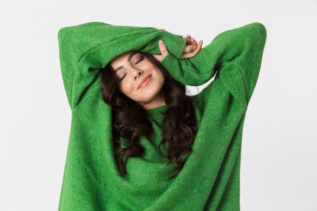 白い壁に隔離のポーズをとって緑のセーターを着た美しい若い女性。