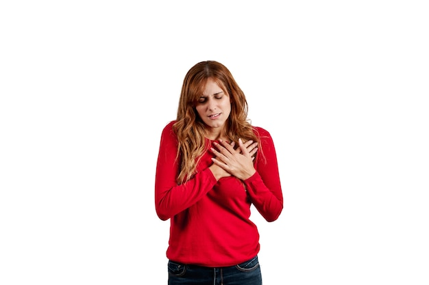 Beautiful young woman dressed in a red sweater, with chest pain, isolated on a white background.