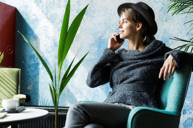 Beautiful young woman dressed in sweater and hat sitting in chair at the cafe table, talking on mobile phone, stylish interior